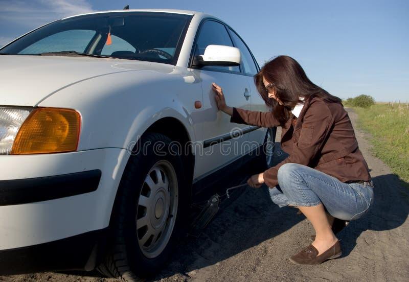 Neumático cambiante de la mujer. imagen de archivo