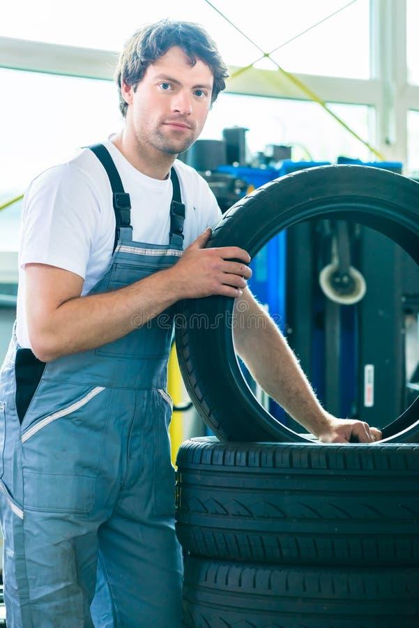 Neumático cambiante del mecánico de automóviles en taller fotos de archivo