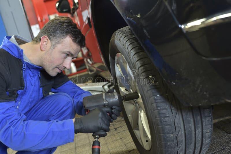 Neumático cambiante del mecánico en el coche fotografía de archivo