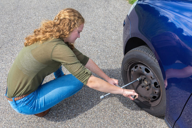 Neumático de coche cambiante de la mujer holandesa joven en el camino imagen de archivo