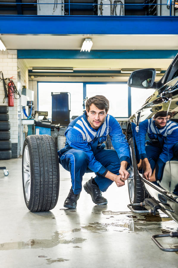 Neumático de coche de Crouching While Changing del mecánico en el garaje imágenes de archivo libres de regalías