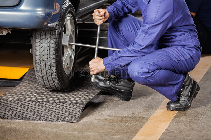 Neumático de coche de Crouching While Fixing del mecánico fotos de archivo libres de regalías