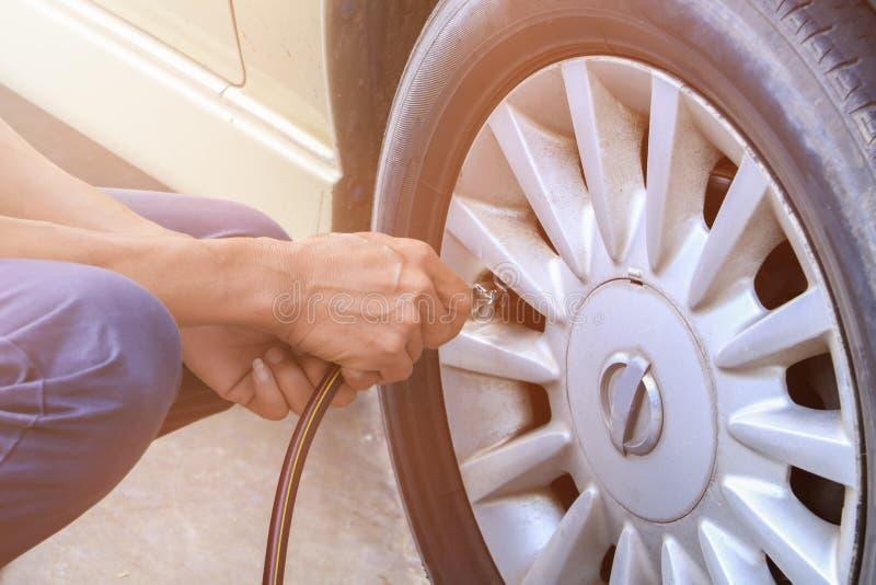 Neumático de comprobación y de relleno de la mano del aire en rueda vieja fotografía de archivo