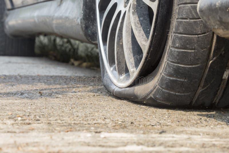 Neumático desinflado del coche en el camino foto de archivo