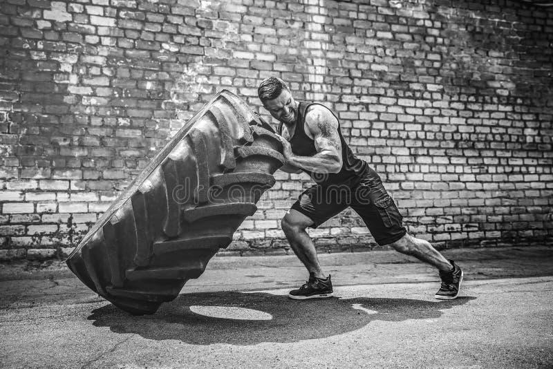 Neumático grande móvil del hombre descamisado muscular de la aptitud imagen de archivo libre de regalías