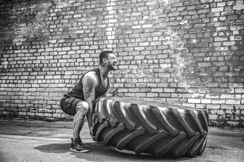 Neumático grande móvil del hombre descamisado muscular de la aptitud imagenes de archivo