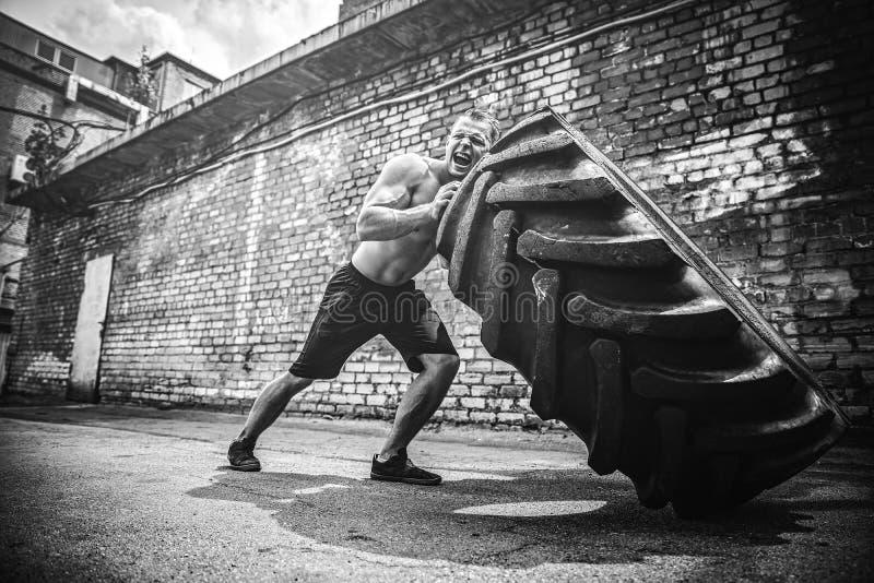 Neumático grande móvil del hombre descamisado muscular de la aptitud fotos de archivo libres de regalías