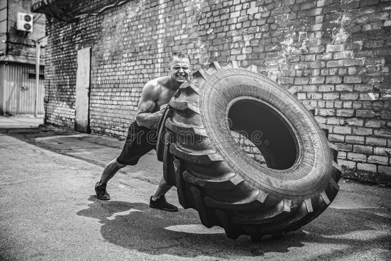 Neumático grande móvil del hombre descamisado muscular de la aptitud fotografía de archivo