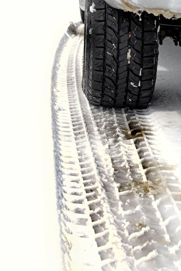 Neumático y pistas de coche en nieve imagen de archivo