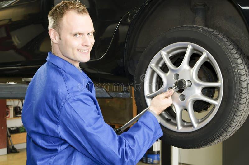 Neumáticos cambiantes del hombre en el garage fotos de archivo libres de regalías