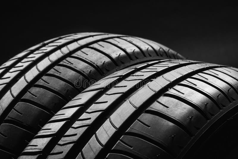 Neumáticos de coche económicos en combustible del verano en fondo negro imágenes de archivo libres de regalías
