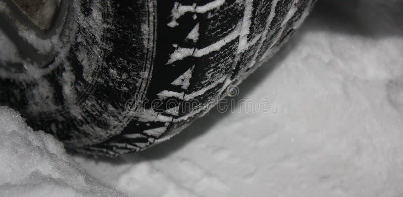 Neumáticos de coche en el camino del invierno cubierto con nieve imagen de archivo