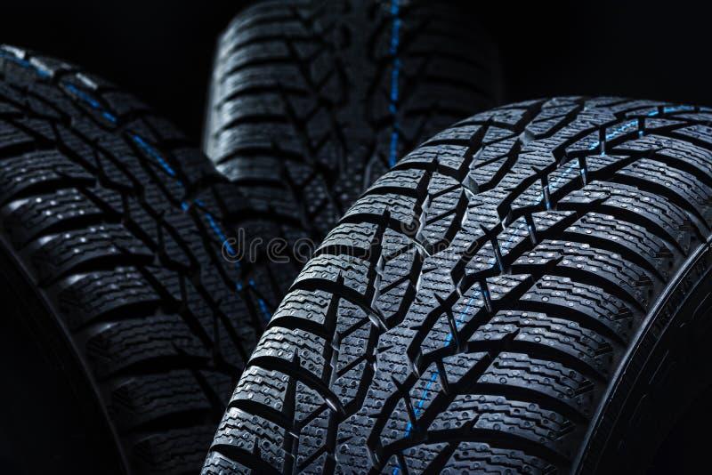 Neumáticos del invierno en fondo negro con la iluminación contrasty foto de archivo libre de regalías