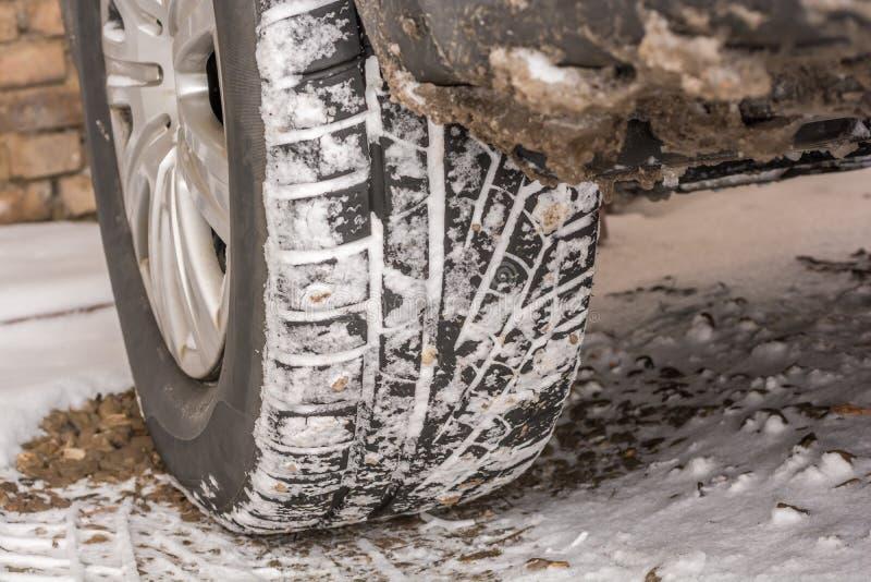 Neumáticos del invierno en la nieve en un coche imagen de archivo