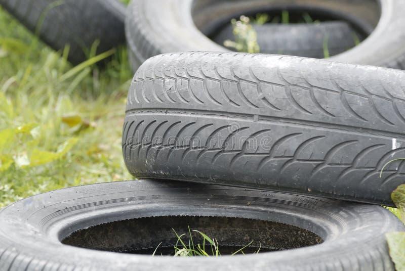 Neumáticos inútiles vaciados en prado. imagen de archivo libre de regalías