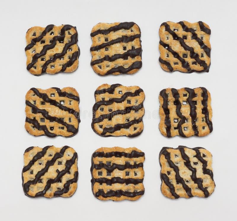 Neun Plätzchen bedeckt mit Schokoladenzuckerglasur lizenzfreies stockfoto