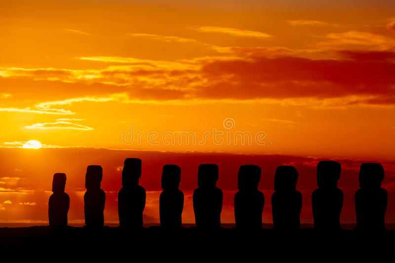 Neun stehende moais bei rotem und goldenem Sonnenuntergang lizenzfreie stockbilder