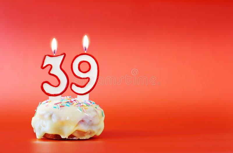 Neununddreißig Jahre Geburtstag Kleiner Kuchen mit weißer brennender Kerze in Form von Nr. 39 lizenzfreie stockbilder