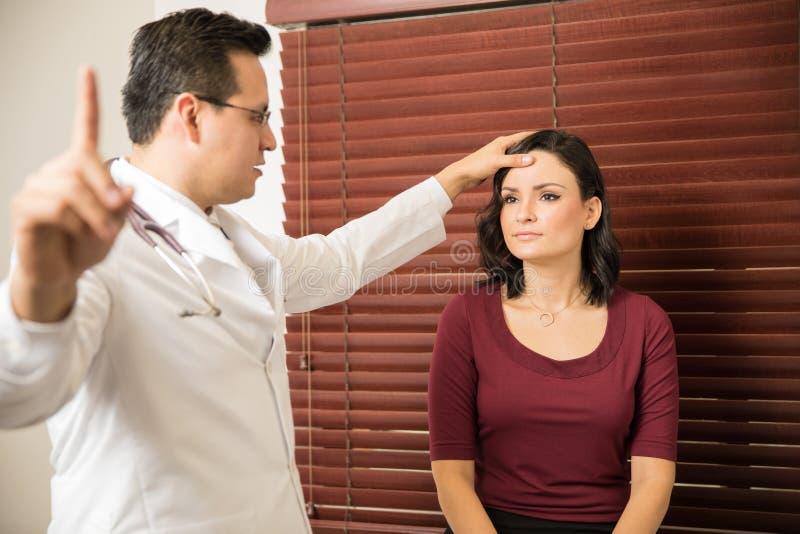 Neurólogo que examina al paciente femenino fotos de archivo
