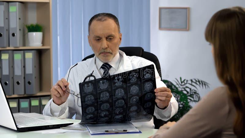 Neurochirurg die hersenenröntgenstraal waarnemen, die patiënt over ernstige ziekte gaan vertellen royalty-vrije stock fotografie