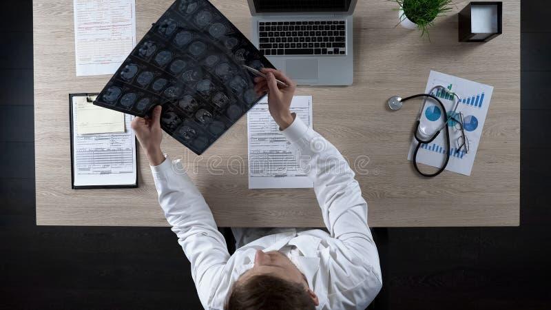 Neurochirurgien regardant l'esprit humain IRM pour diagnostiquer la maladie patiente, vue supérieure photos libres de droits