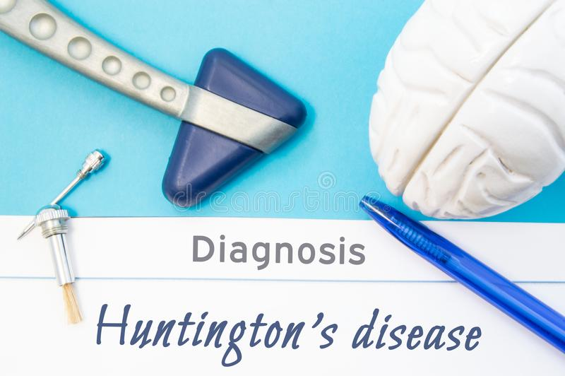 Neurological diagnosis of Huntington`s disease. Neurological hammer, human brain figure, tools for sensitivity testing are on tabl. E next to title of text royalty free stock photos