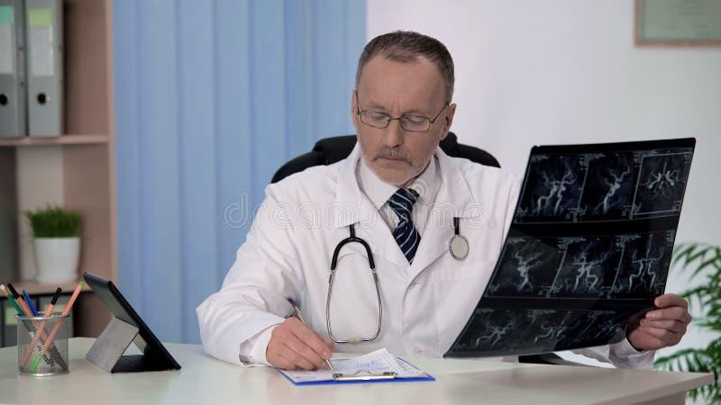 Neurologue vérifiant l'angiographie des vaisseaux sanguins, écrivant la prescription sous la forme image stock