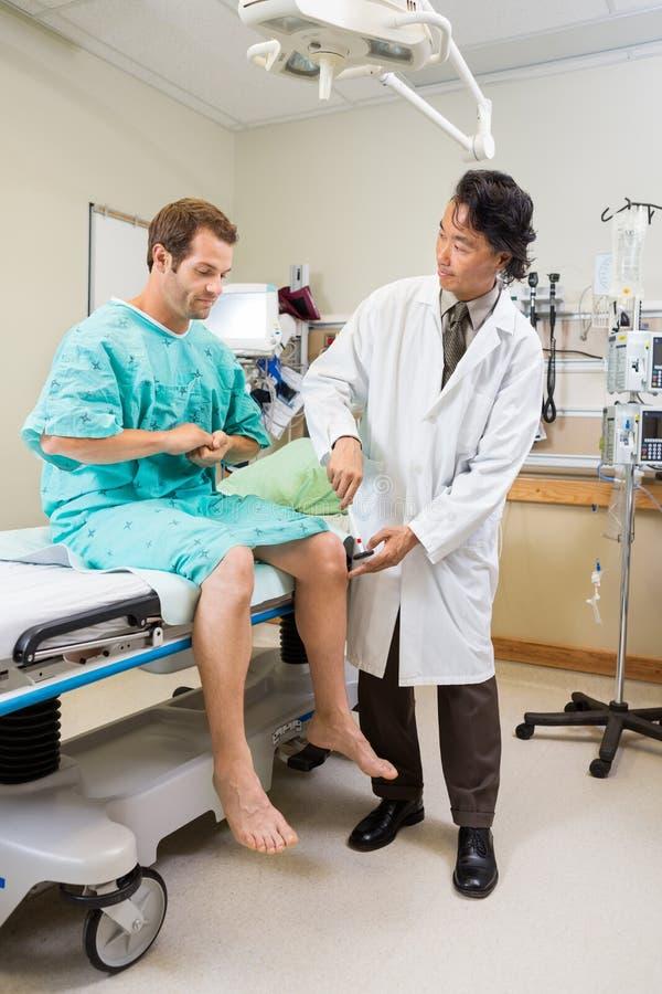 Neuroloog die de Knie van de Patiënt met Hamer onderzoeken royalty-vrije stock afbeeldingen