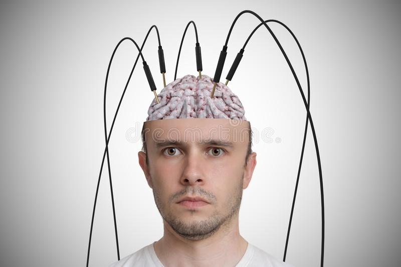 Neuroscience and brain research concept. Young man has cables and electrodes in his brain royalty free stock images
