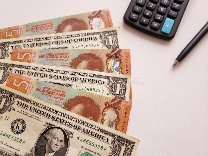 Neuseeländische Banknoten, amerikanische Ein-Dollar-Scheine, Taschenrechner, Kugelschreiber und weißer Hintergrund stockfotografie