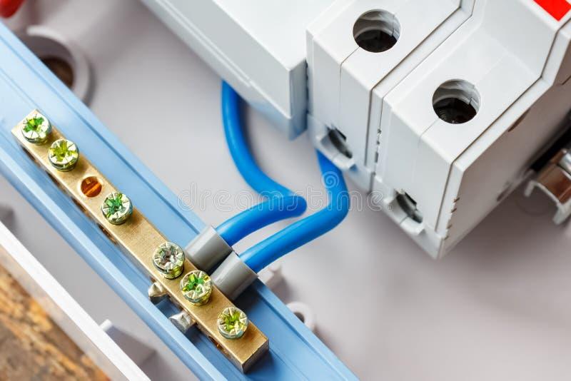 Neutral buss förbindelse av blåa trådar i den vita plast- monterande askcloseupen arkivbild