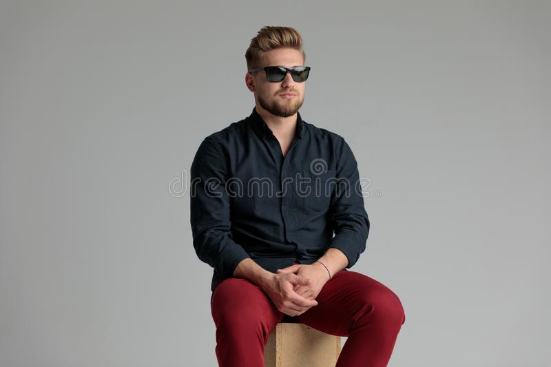 Neutral casual man looking away and holding his hands. Together while wearing a blue shirt and red jeans, sitting on gray studio background stock images