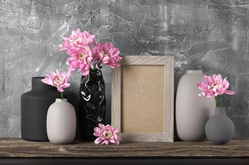 Neutral colored home decor. Pink flowers in neutral colored vases and frame on distressed wooden shelf against rough plaster grey wall. Home decor stock image