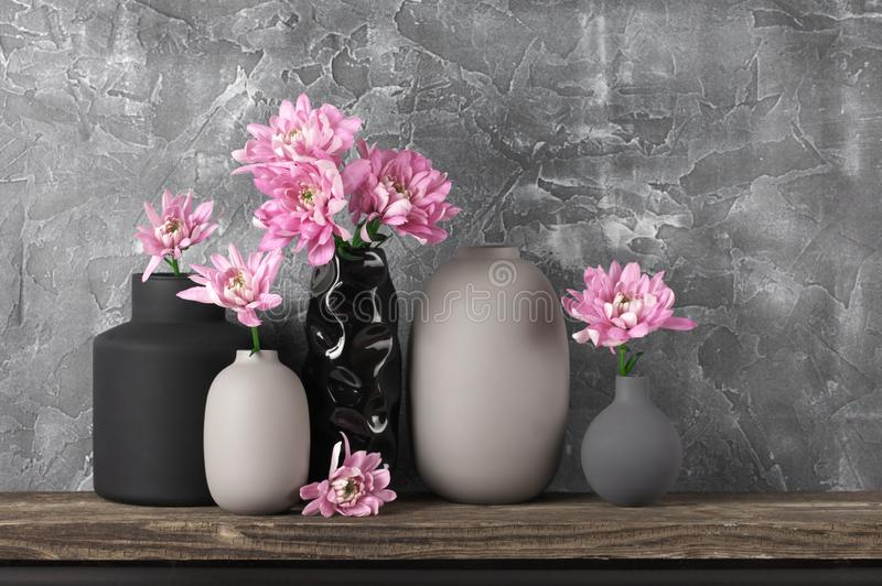 Neutral colored home decor. Pink flowers in neutral colored vases on distressed wooden shelf against rough plaster grey wall. Home decor royalty free stock images