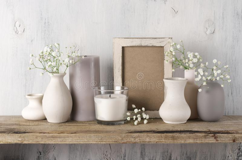 Neutral colored home decor. White flowers in neutral colored vases, candles and frame on rustic wooden shelf against shabby white wall. Home decor stock images