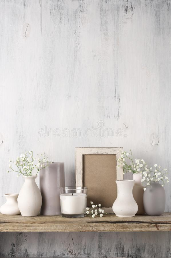 Neutral colored home decor. White flowers in neutral colored vases, candles and frame on rustic wooden shelf against shabby white wall. Home decor royalty free stock image