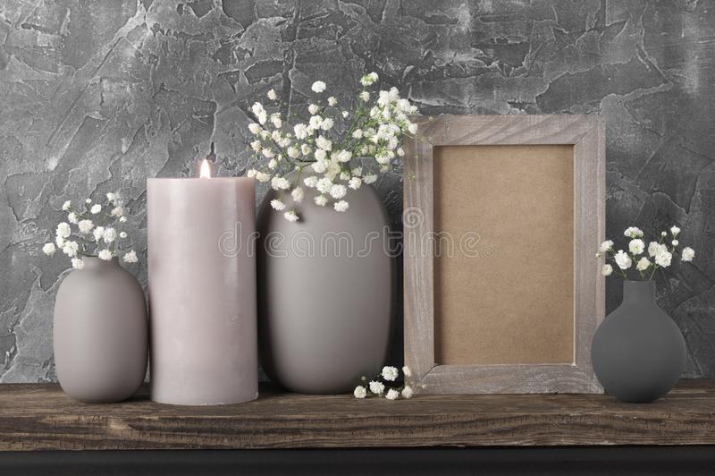 Neutral colored home decor. White flowers in neutral colored vases, frame and burned candles on distressed wooden shelf against rough plaster grey wall. Home royalty free stock images