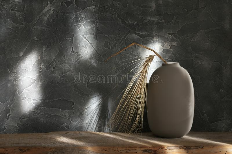 Neutral colored vases, home decor. Neutral colored vase with ear on distressed wooden shelf against rough plaster dark grey wall in sunlight. Home decor royalty free stock photo