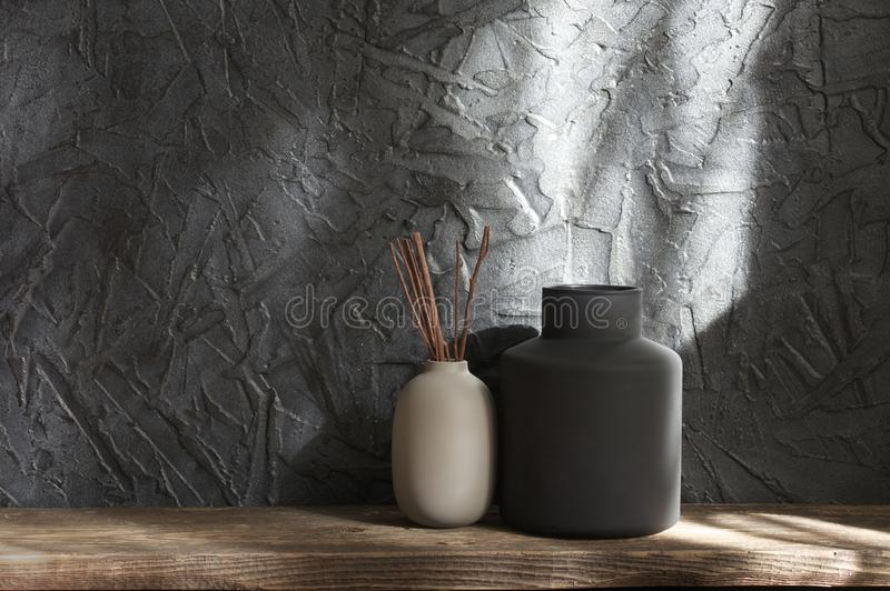 Neutral colored vases, home decor. Neutral colored vases on distressed wooden shelf against rough plaster dark grey wall in sunlight. Home decor stock photos