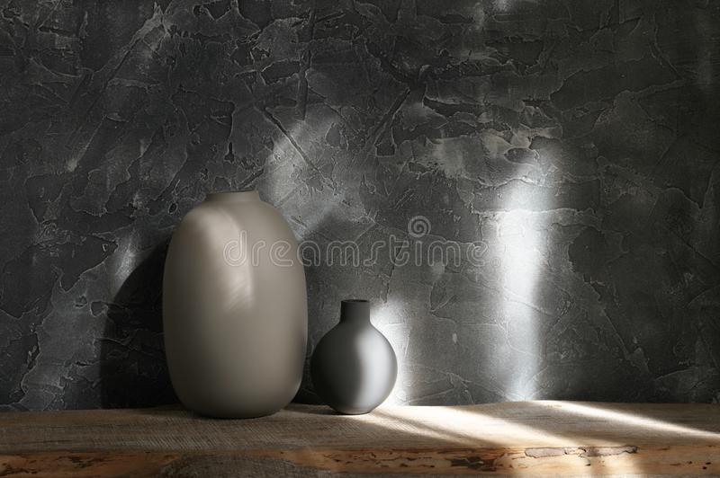 Neutral colored vases, home decor. Neutral colored vases on distressed wooden shelf against rough plaster dark grey wall in sunlight. Home decor stock photo