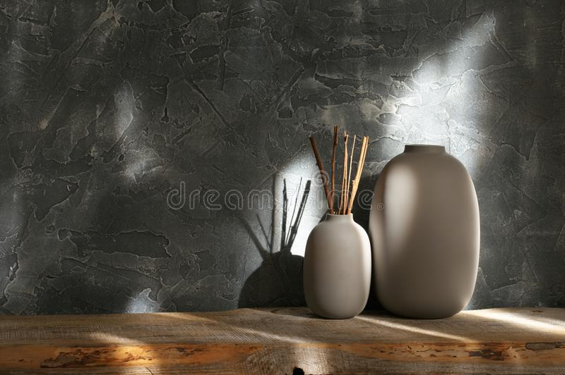 Neutral colored vases, home decor. Neutral colored vases with wood sticks on distressed wooden shelf against rough plaster dark grey wall in sunlight. Home decor royalty free stock photo