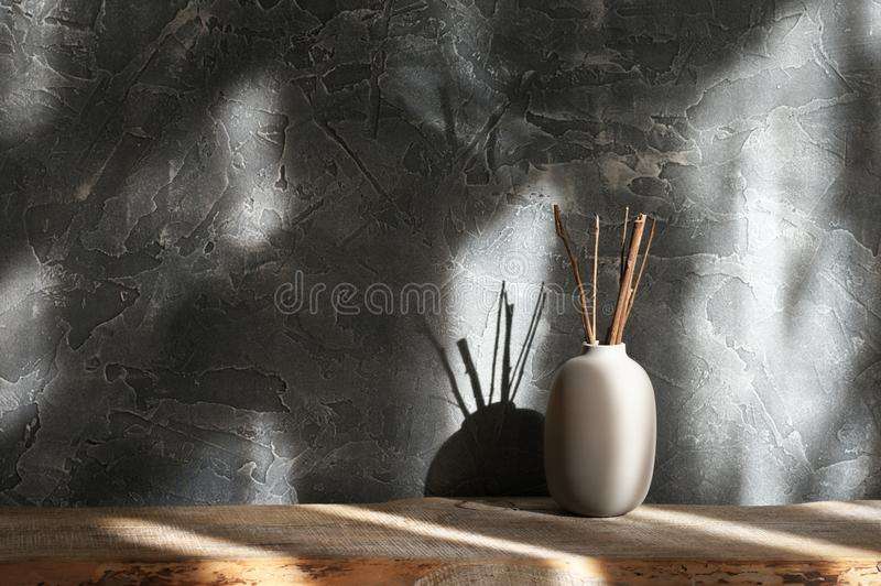 Neutral colored vases, home decor. Neutral colored vase with wood sticks on distressed wooden shelf against rough plaster dark grey wall in sunlight. Home decor stock images