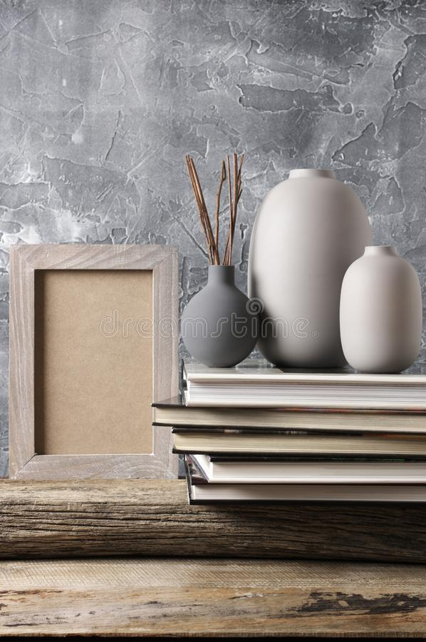 Neutral colored home decor. Neutral colored vases, shabby photoframe and stack of books on distressed wooden shelf against rough plaster grey wall. Home decor royalty free stock photo