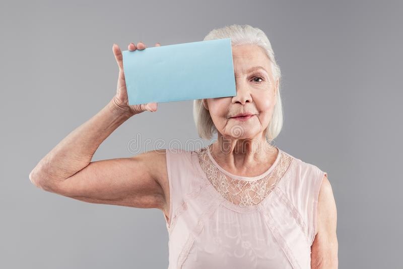 Neutral grey-haired old woman wearing nude clothes and attaching blue nameplate royalty free stock photography