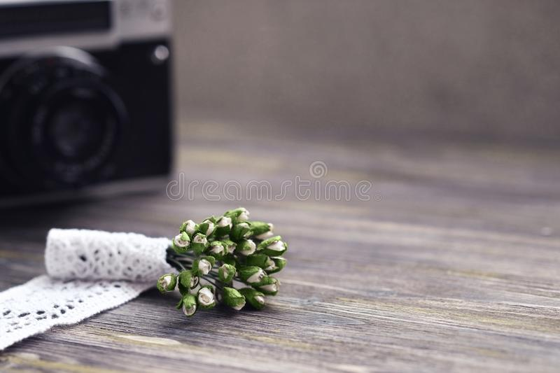 Neutral toning. Flatlay. Bouquet of synthetic lilies of the valley in white lace lies on wooden vintage/rustic background. On the background is retro camera royalty free stock photography