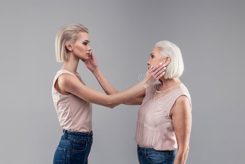 Neutralnej młodej blondynki dziewczyny pieszczotliwy policzek jej starsza matka zdjęcie royalty free
