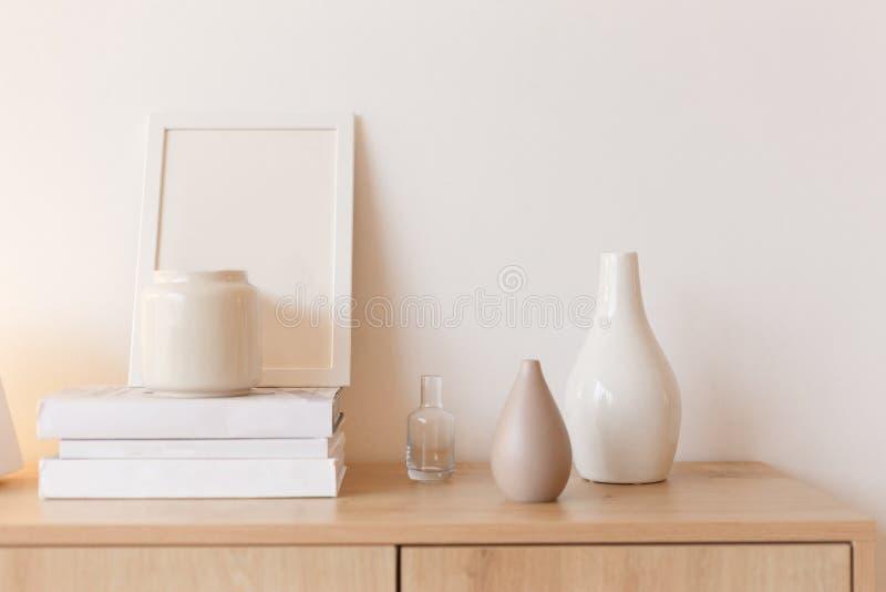 Neutralt färgade vaser, fotoramen och bunten av böcker på byråhylla arkivfoto