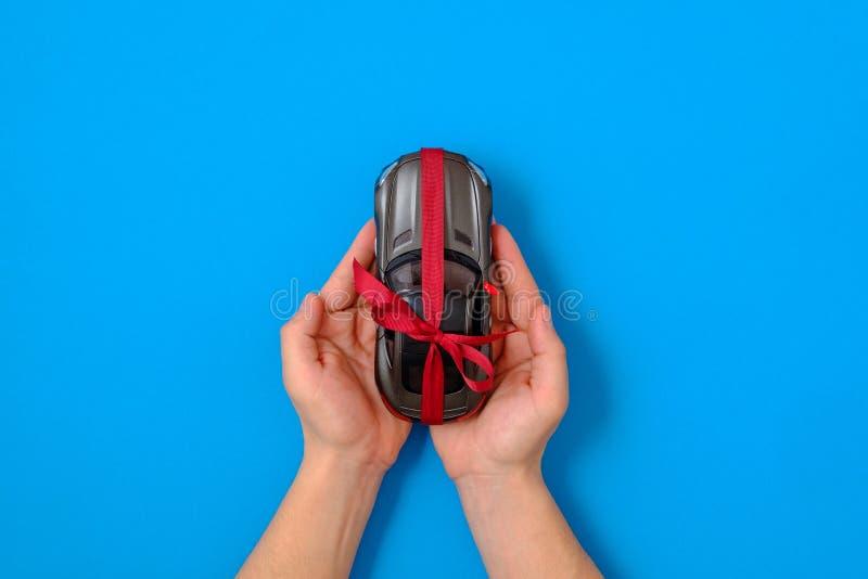 Neuwagengeschenkkonzept Spielzeugautomodell gebunden mit einem roten Band und einem Bogen in den menschlichen Händen auf blauem  stockbilder