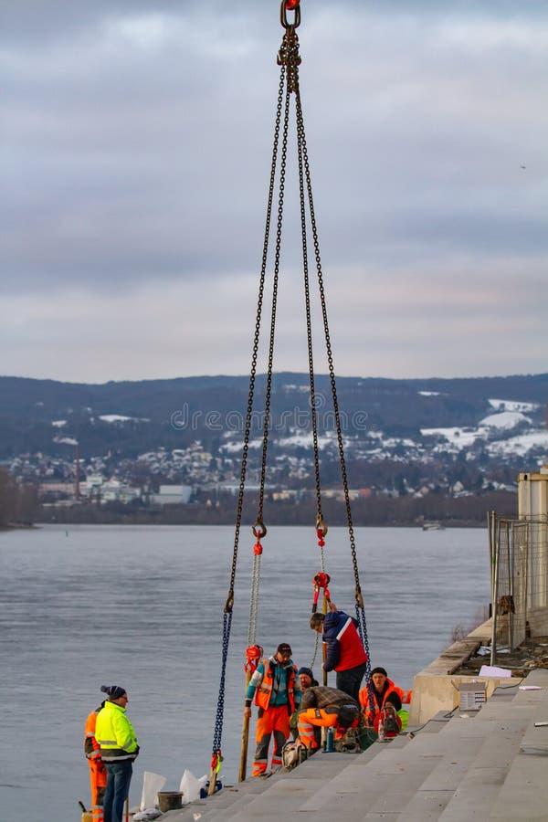Neuwied, Γερμανία - 1 Φεβρουαρίου 2019: οι εργάτες οικοδομών καθορίζουν ένα βήμα μιας σκάλας στην ακτή ενός ποταμού στοκ εικόνα με δικαίωμα ελεύθερης χρήσης