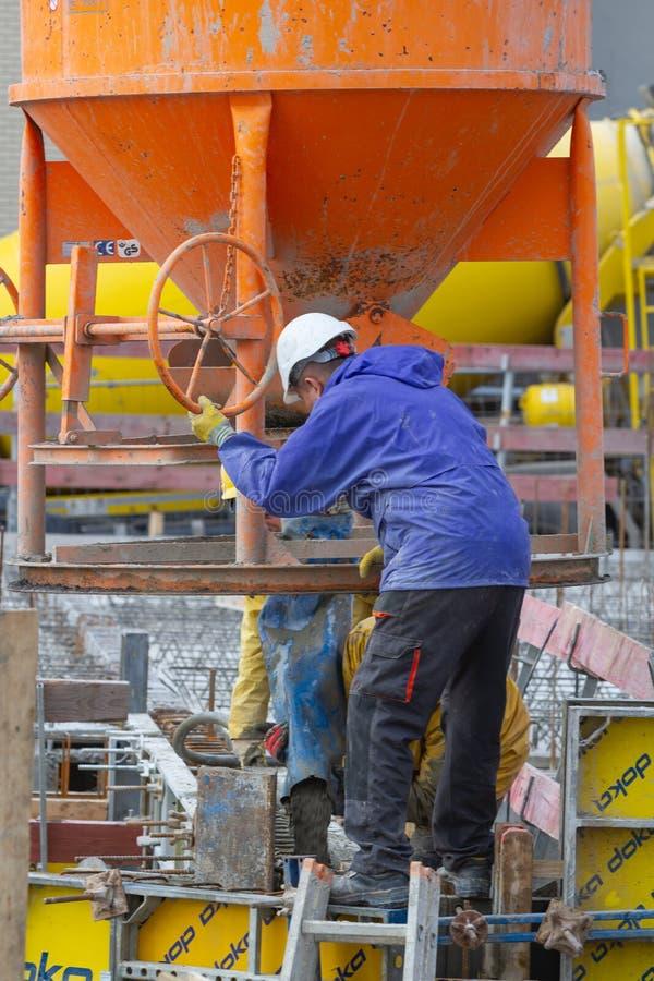 Neuwied, Alemanha - 1º de fevereiro de 2019: os trabalhadores da construção estão enchendo o almofariz em segmentos do pre-molde  foto de stock